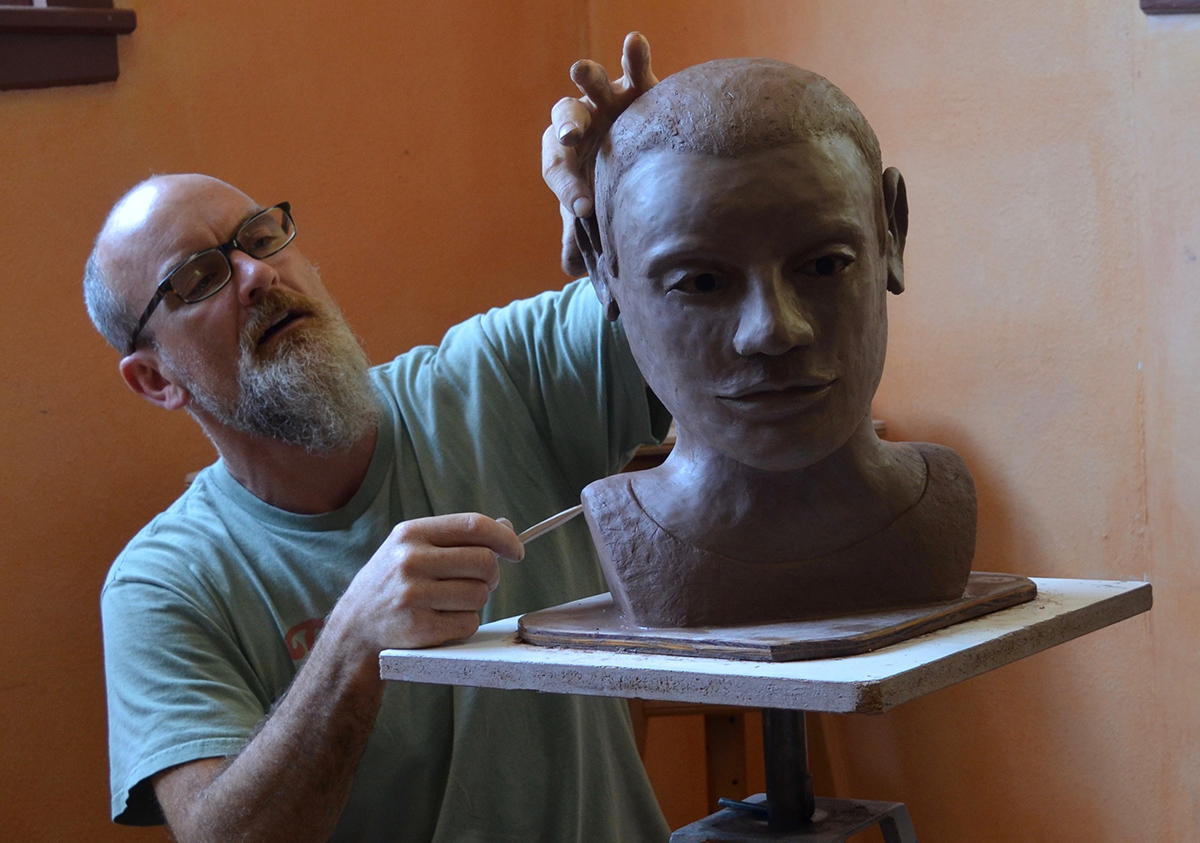 A man working on a clay bust