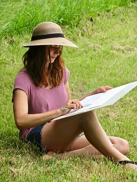 A woman sitting in a field drawing