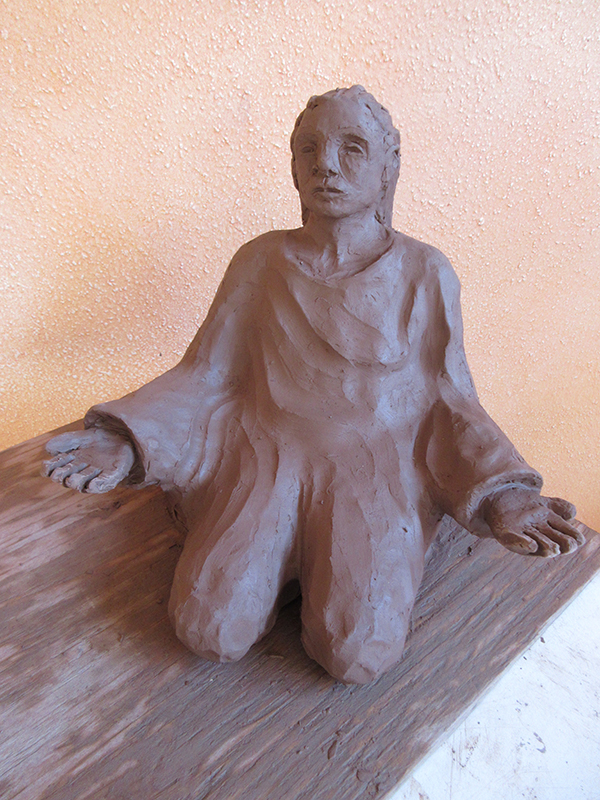 clay figurine bent on knees with outstretched arms