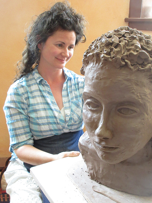 a woman working on a clay bust