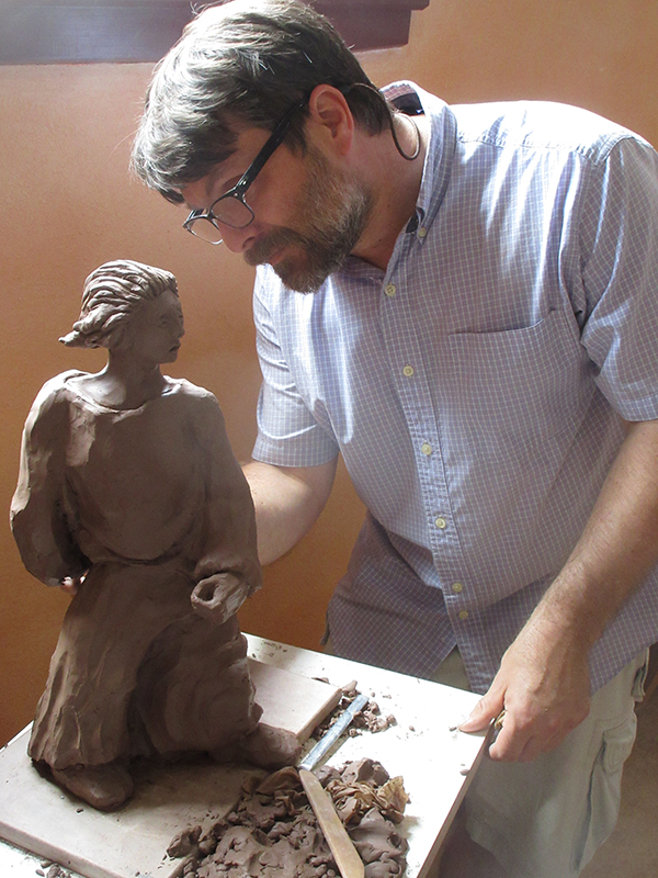 a man working on a clay figurine of a woman