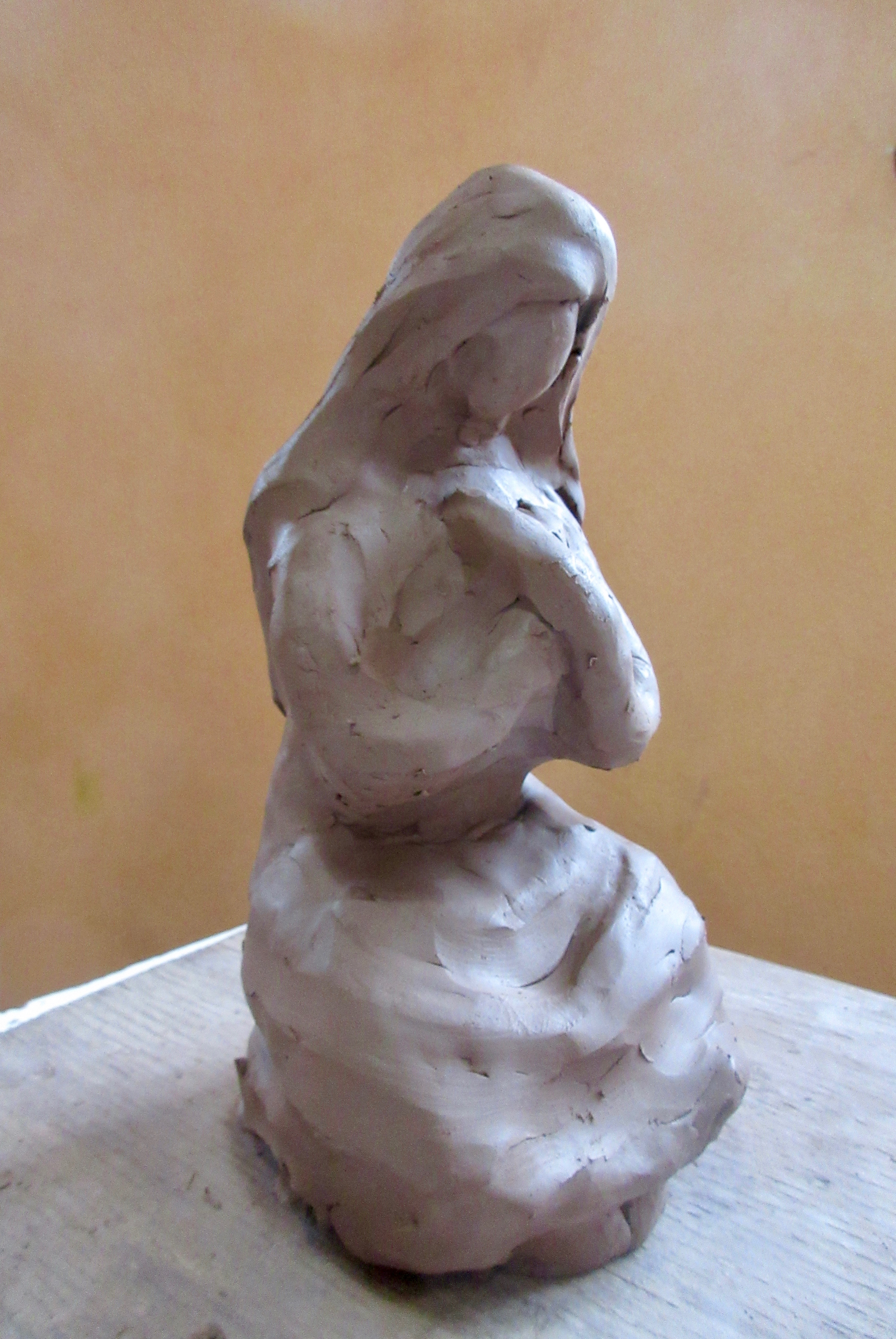 a clay figuring with crossed arms