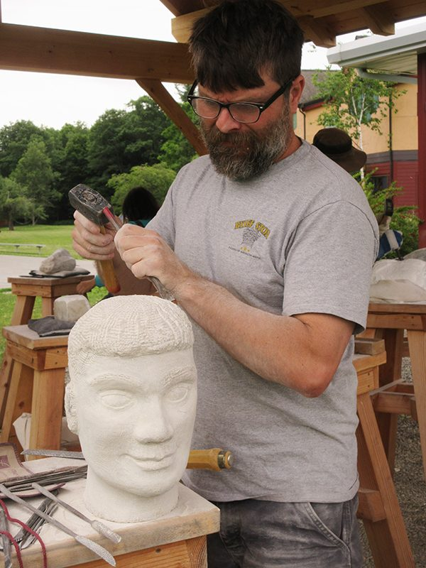 Alkion summer student working sculpting human head from stone