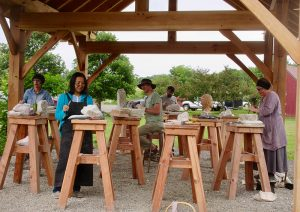 Students working outdoors on stone carving projects during Alkion summer courses