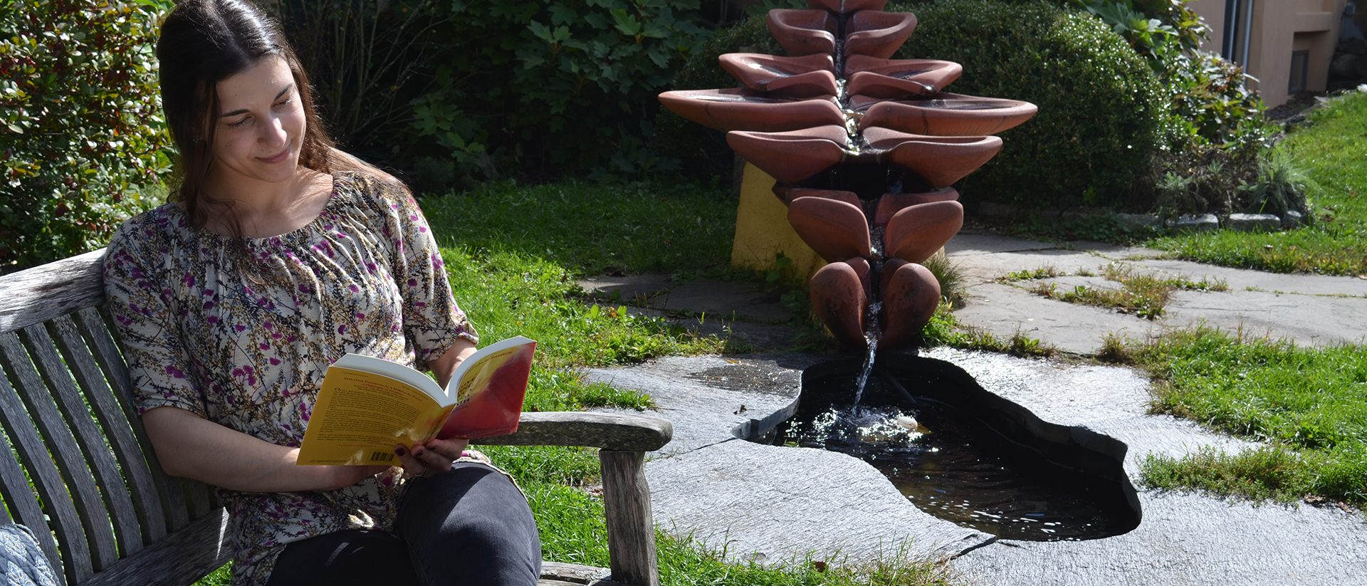Waldorf teacher ed student outside reading near water sculpture