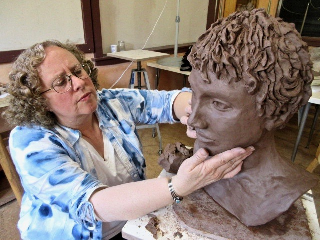 student working on clay head sculpture