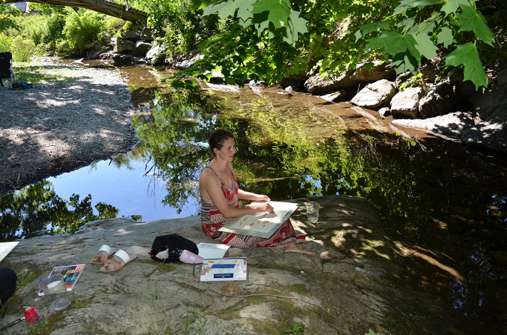 Alkion student drawing in a natural setting near water